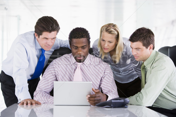 Four businesspeople in a boardroom looking at laptop Stock photo © monkey_business