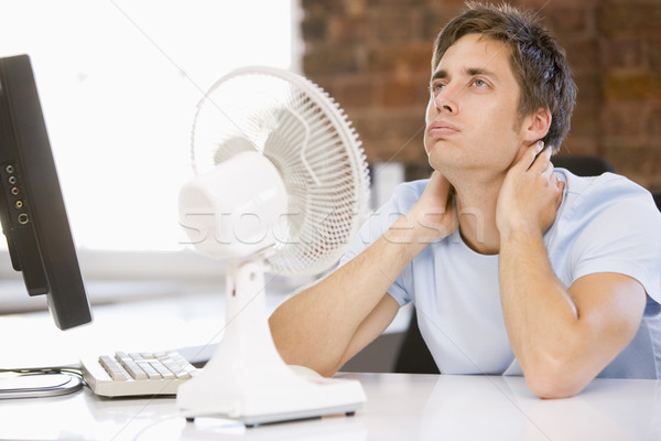 Businessman in office with computer and fan cooling off Stock photo © monkey_business