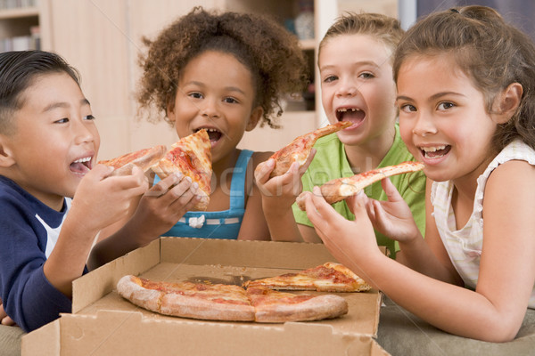 Four young children indoors eating pizza smiling Stock photo © monkey_business