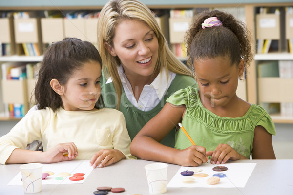 Kindergarten teacher sitting with students in art class Stock photo © monkey_business