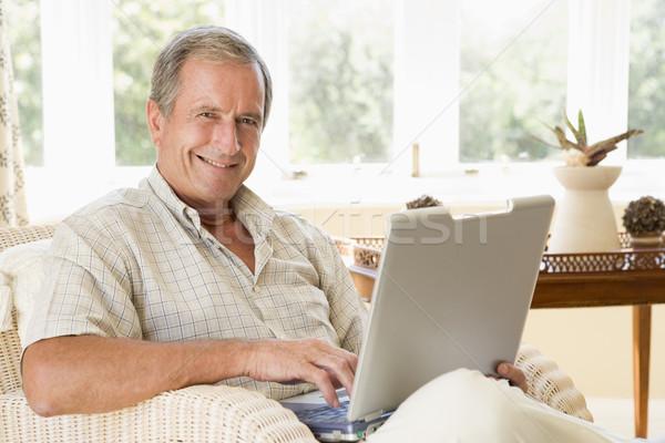 Férfi nappali laptop mosolyog boldog technológia Stock fotó © monkey_business
