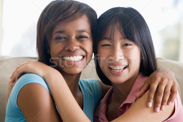 Dois sorridente amigos meninas sofá Foto stock © monkey_business