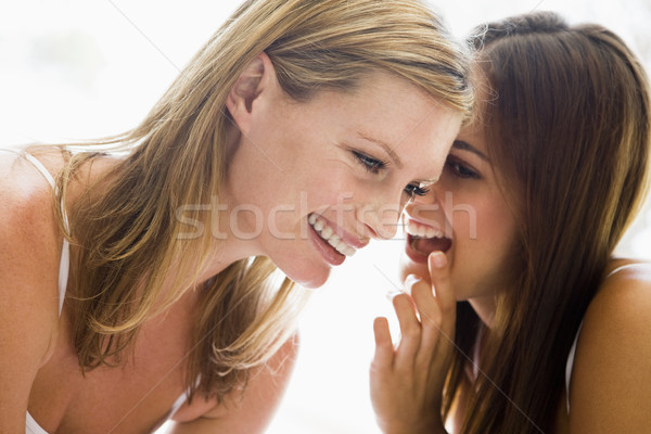 Two women whispering and smiling Stock photo © monkey_business