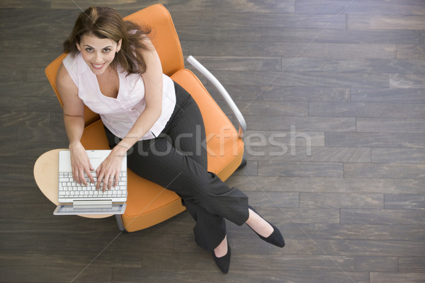 Businesswoman sitting indoors with laptop smiling Stock photo © monkey_business