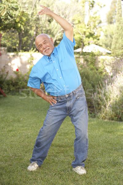 Senior Man Exercising In Garden Stock photo © monkey_business
