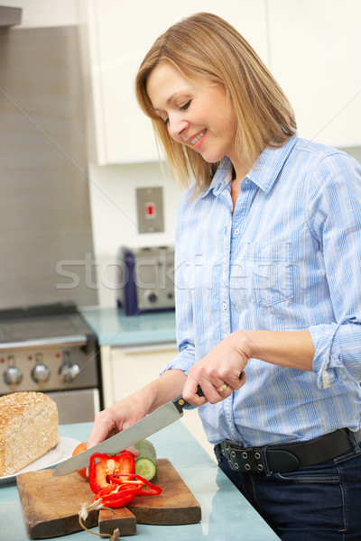 Woman chopping vegetables in domestic kitchen Stock photo © monkey_business