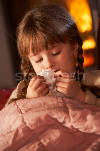 Sick Girl With Cold Resting On Sofa By Cosy Log Fire Stock photo © monkey_business