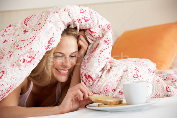 Pretty Woman Snuggled Under Duvet Eating Breakfast Stock photo © monkey_business