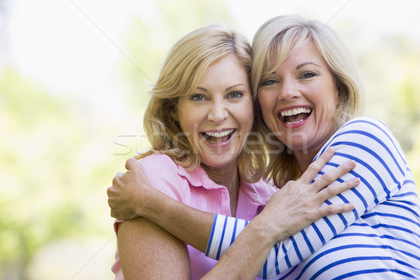 Two women outdoors hugging and smiling Stock photo © monkey_business