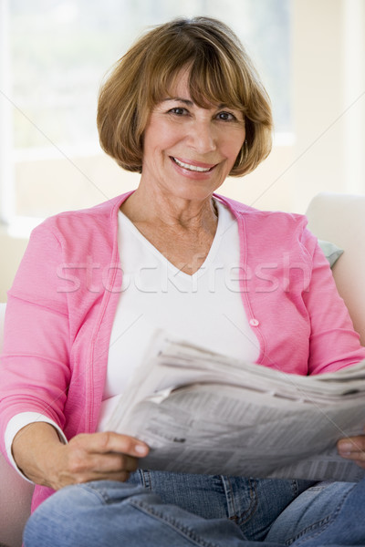 Woman relaxing with newspaper in living room and smiling Stock photo © monkey_business