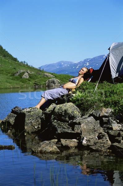 Stock fotó: Fiatal · nő · napozás · kövek · tó · kő · hegyek