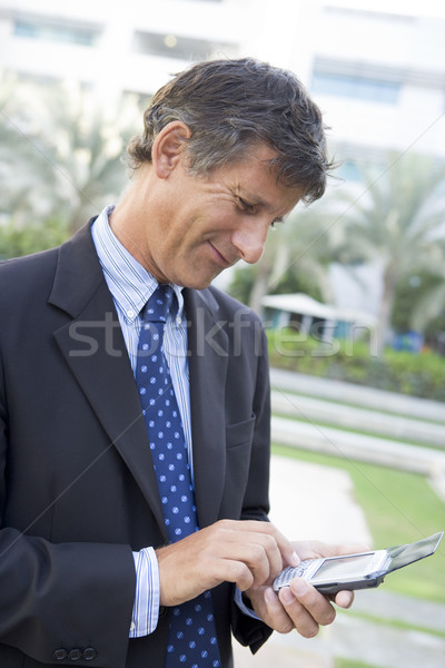 Businessman outdoors using personal digital assistant smiling Stock photo © monkey_business