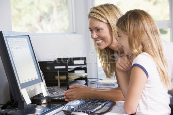 Woman and young girl in home office with computer smiling Stock photo © monkey_business