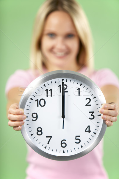 Woman Holding Clock Showing 12 O'Clock Stock photo © monkey_business