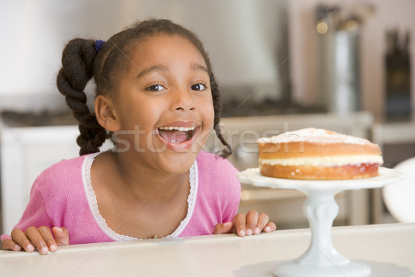 Stock photo: Young girl in kitchen looking at cake on counter smiling