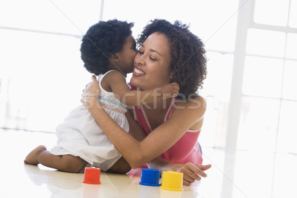Mother and daughter indoors kissing and smiling Stock photo © monkey_business