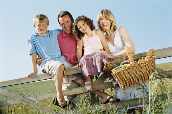 Family outdoors by fence with picnic basket smiling Stock photo © monkey_business