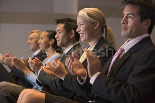 Five businesspeople applauding and smiling in presentation room Stock photo © monkey_business