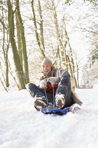 Man Sledging Through Snowy Woodland Stock photo © monkey_business