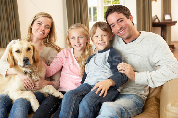 Happy young family sitting on sofa holding a dog Stock photo © monkey_business
