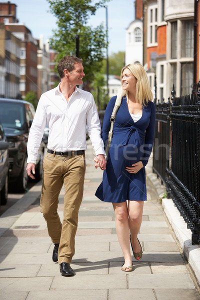 Couple With Pregnant Wife Walking Along Urban Sidewalk Stock photo © monkey_business
