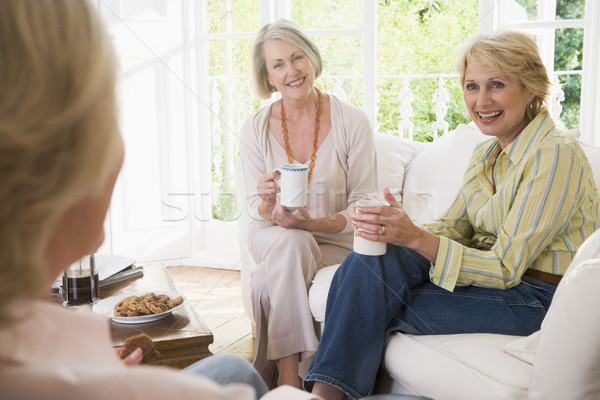 Three women in living room with coffee smiling Stock photo © monkey_business