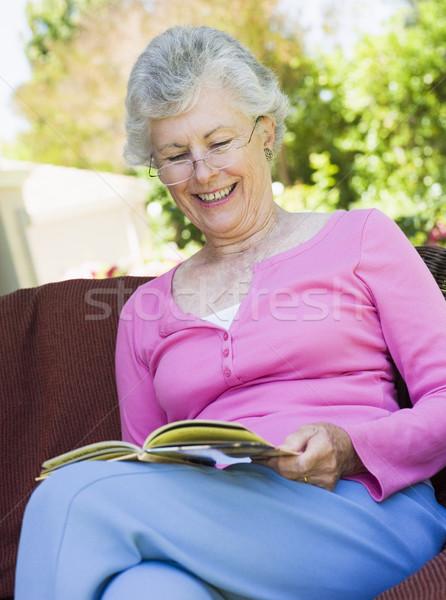 Stock photo: Senior woman reading book outside