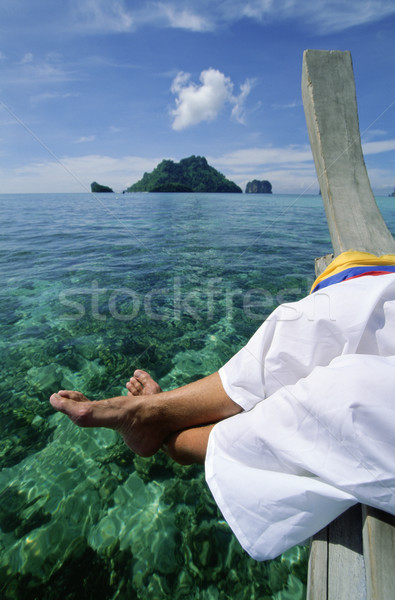 Man on pier dangling feet over clear water Stock photo © monkey_business