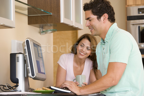 Couple in kitchen with computer and coffee smiling Stock photo © monkey_business