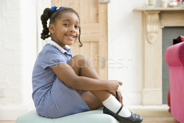 Young girl in front hallway fixing shoe and smiling Stock photo © monkey_business