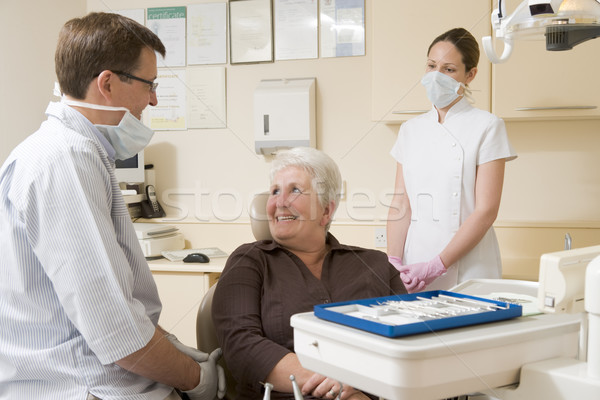 Dentist and assistant in exam room with woman in chair smiling Stock photo © monkey_business