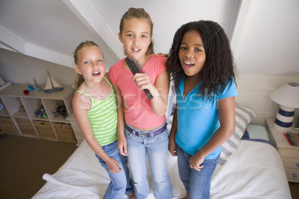 Three Young Girls Standing On A Bed, Singing Into A Hairbrush Stock photo © monkey_business