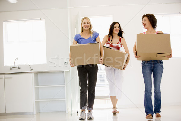 Stock photo: Three girl friends moving into new home smiling