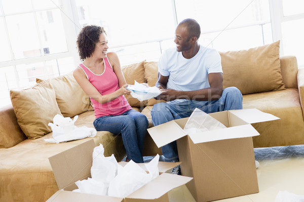 Couple unpacking boxes in new home smiling Stock photo © monkey_business