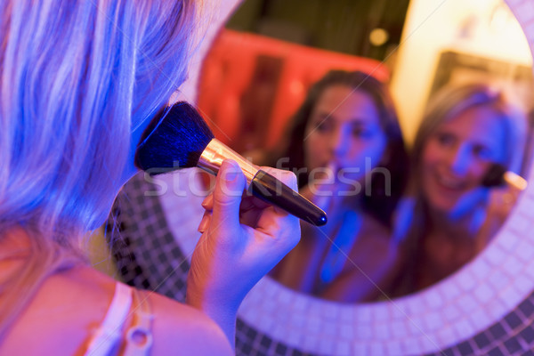 Two young women applying makeup in a nightclub bathroom Stock photo © monkey_business
