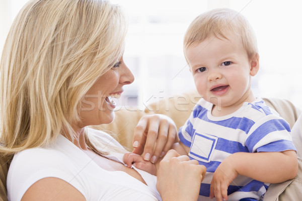 Mother in living room holding baby smiling Stock photo © monkey_business