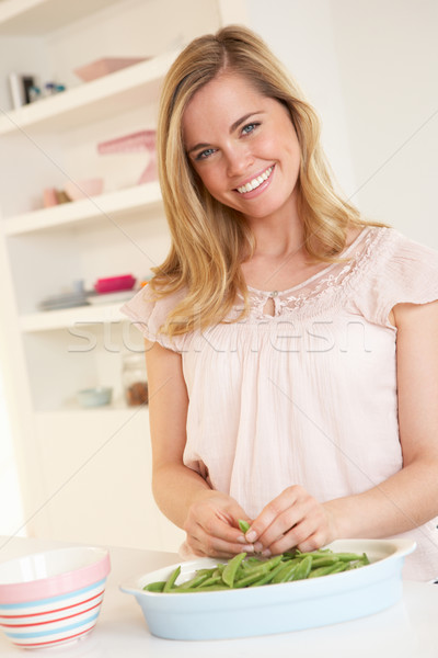 Young woman splitting pea in kitchen Stock photo © monkey_business