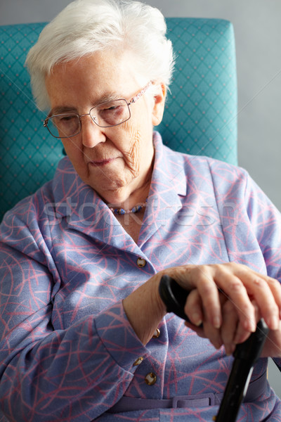 Unhappy Senior Woman Sitting In Chair Holding Walking Stick Stock photo © monkey_business