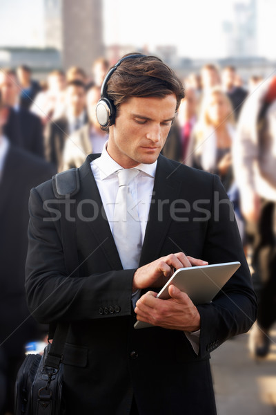 Male commuter in crowd with tablet and headphones Stock photo © monkey_business