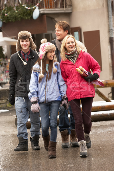Stock photo: Teenage Family Walking Along Snowy Town Street In Ski Resort