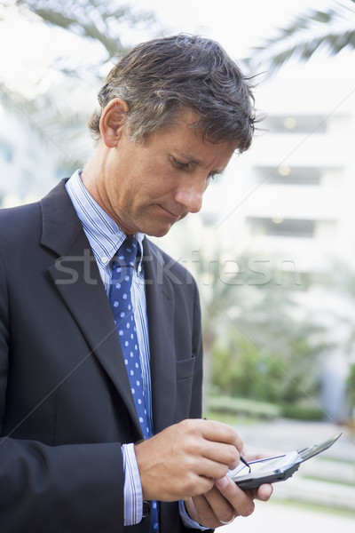Businessman outdoors using personal digital assistant Stock photo © monkey_business