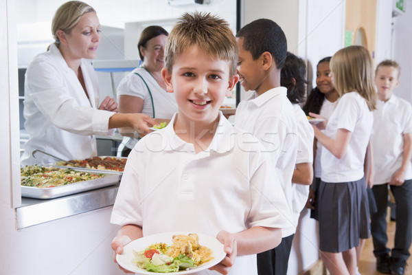 Schoolboy holding plate of lunch in school cafeteria Stock photo © monkey_business