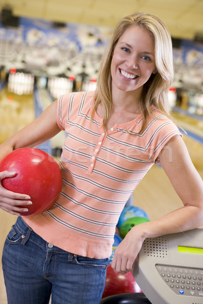 Young woman holding a bowling ball in a bowling alley Stock photo © monkey_business