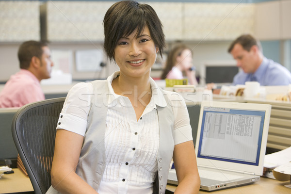 Businesswoman in cubicle smiling Stock photo © monkey_business