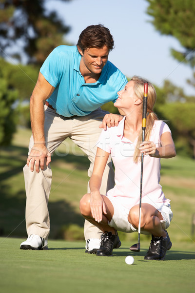 Couple Golfing On Golf Course Lining Up Putt On Green Stock photo © monkey_business