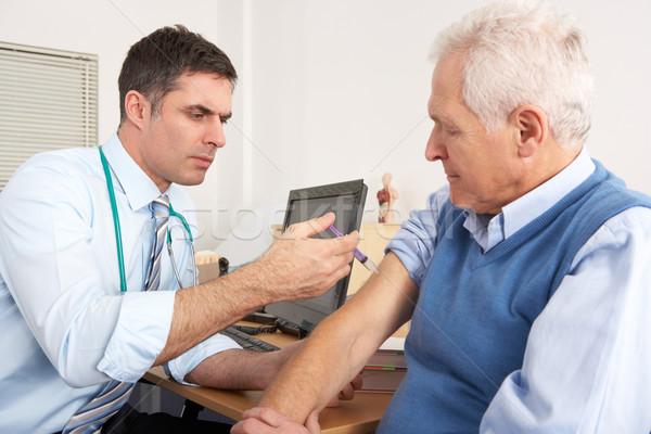 British GP injecting senior man in surgery Stock photo © monkey_business