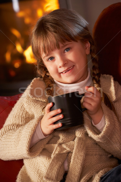 Jong meisje ontspannen warme drank gezellig brand meisje Stockfoto © monkey_business