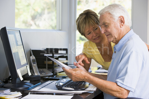 Stock photo: Couple in home office with computer and paperwork