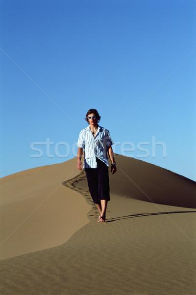 Joven caminando duna arena solitario gafas de sol Foto stock © monkey_business