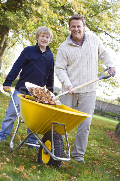 Son helping father to collect leaves Stock photo © monkey_business